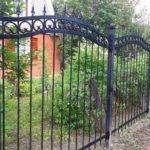 Забор из металлических прутьев возле сада